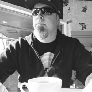 A black and white picture of Jim sitting at a table, wearing a sweatshirt, baseball hat, and sunglasses. Jim looks to the left and out of frame over the top of a steaming cup of coffee.