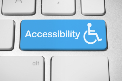 "A keyboard with the return button changed to be blue with the accessibility ""figure in a wheelchair"" logo on it."