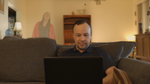 The main character, Michael, sits on a couch in the foreground while the Devil stands in the background behind the couch and looks over his shoulder.