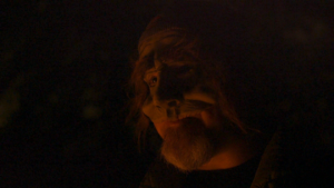 A dark picture of a homeless man in an old man mask. This is a close-up shot of the face of the actor only, and he seems to be lit with a red light.
